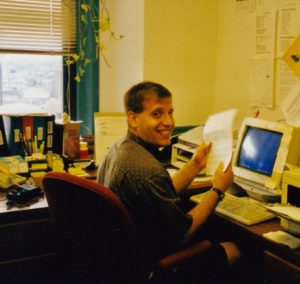 Image of Anthony Galasso sitting a computer desk and smiling
